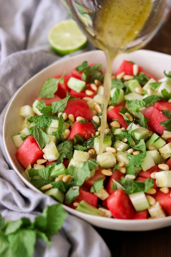 pouring dressing over watermelon salad recipe