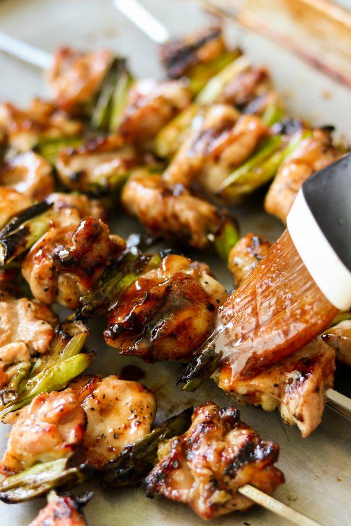 Japanese chicken yakitori sauce getting brushed on chicken