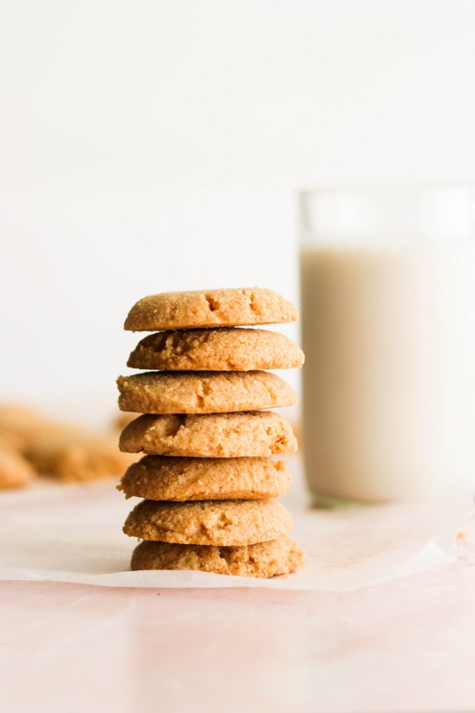 keto vanilla wafers stacked in front of a glass of milk
