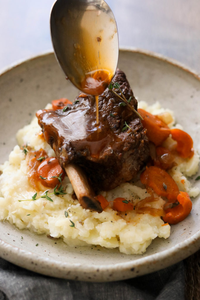 Pouring braising liquid over Whole30 short ribs