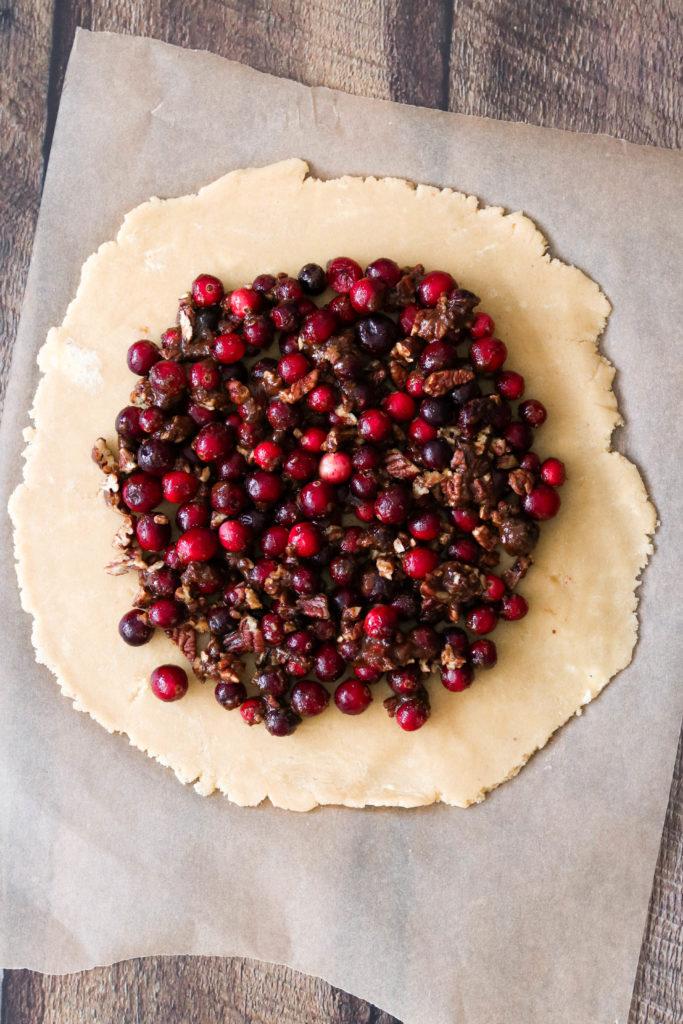 Making of cranberry galette: filling the dough with cranberry filling