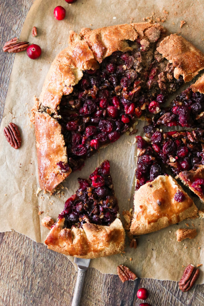Lifting a slice of cranberry galette from parchment paper