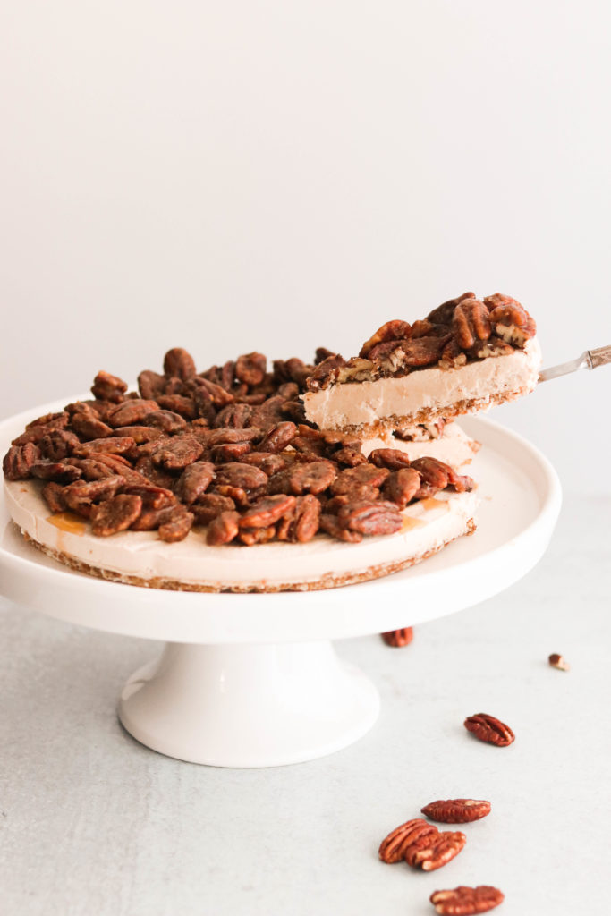 Taking out a slice of easy pecan pie cheesecake on the cakestand