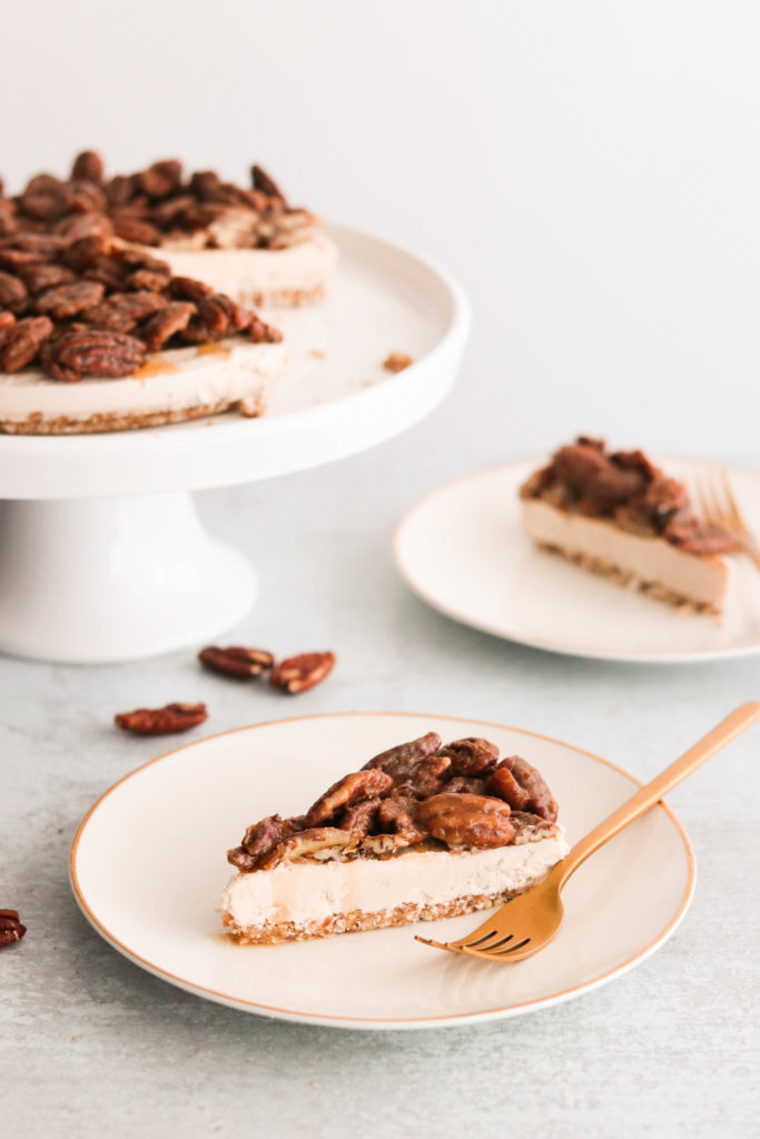 vegan pecan pie cheesecake served on a plate with a gold fork
