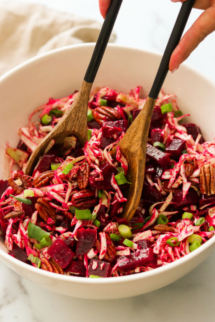 tossing beet slaw together