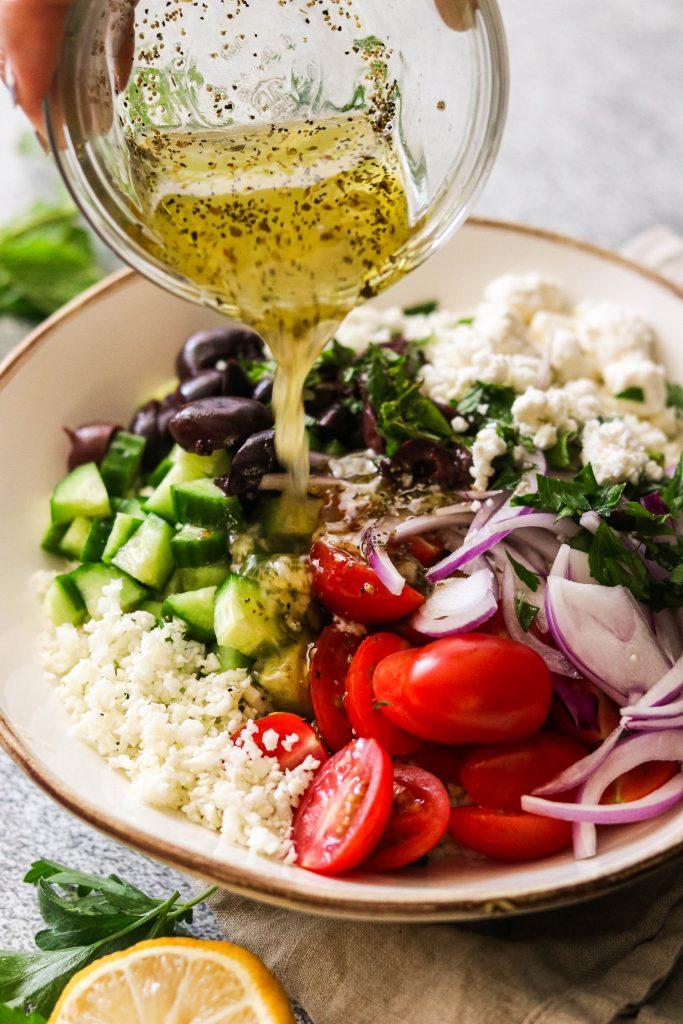 pouring lemon dressing into mediterranean couscous salad