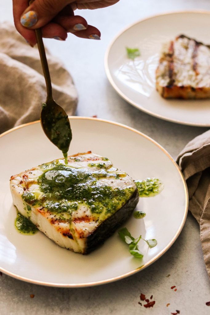 whole30 halibut steak covered in chimichurri sauce with basil