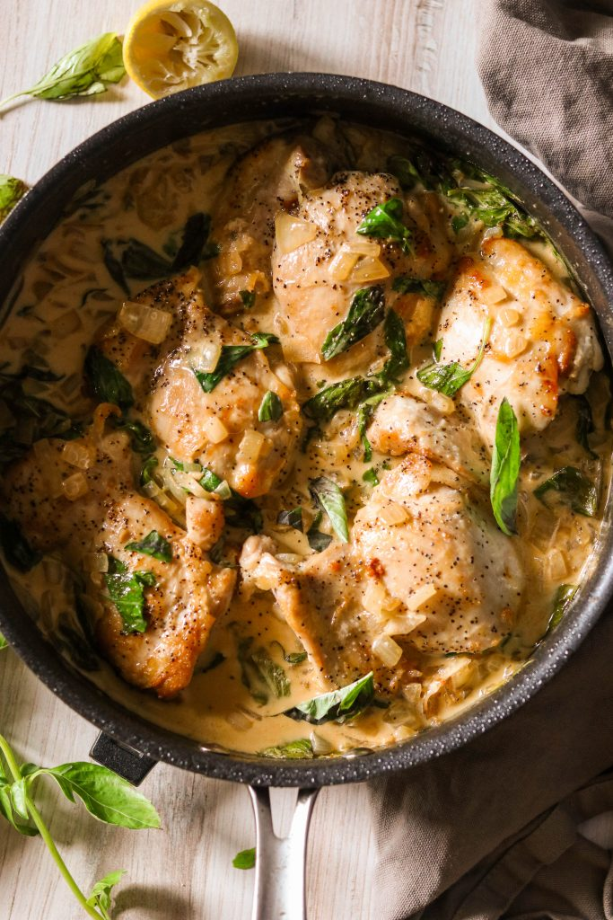 close up of creamy garlic basil chicken in a skillet
