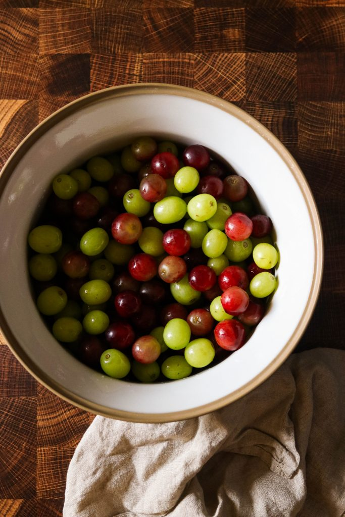 fresh red and green seedless grapes in a bowl