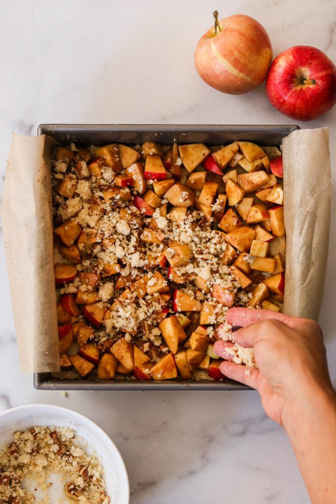 sprinkling crumble layer over paleo apple pie bars