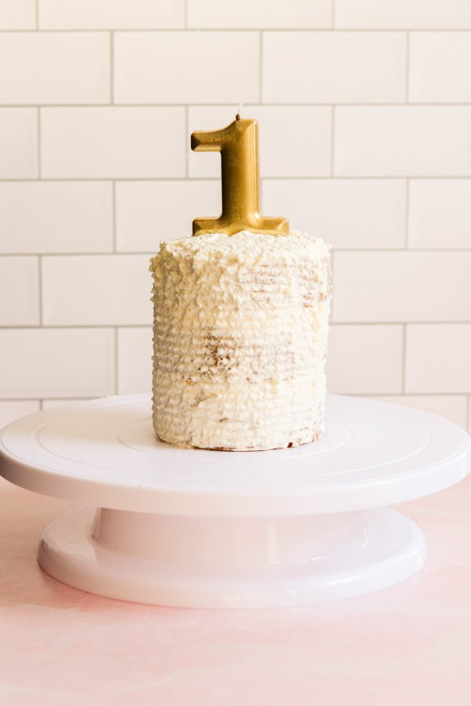Allergen free and paleo smash cake on a cake stand with a birthday candle