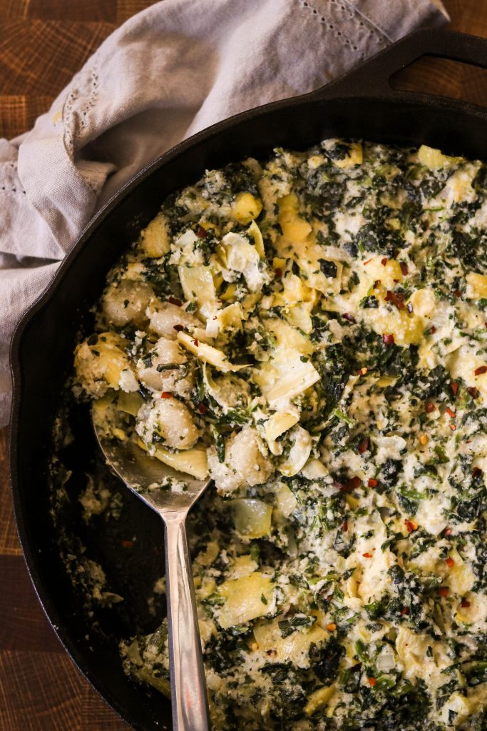 Vegan cauliflower gnocchi baked with creamy spinach and artichoke dip