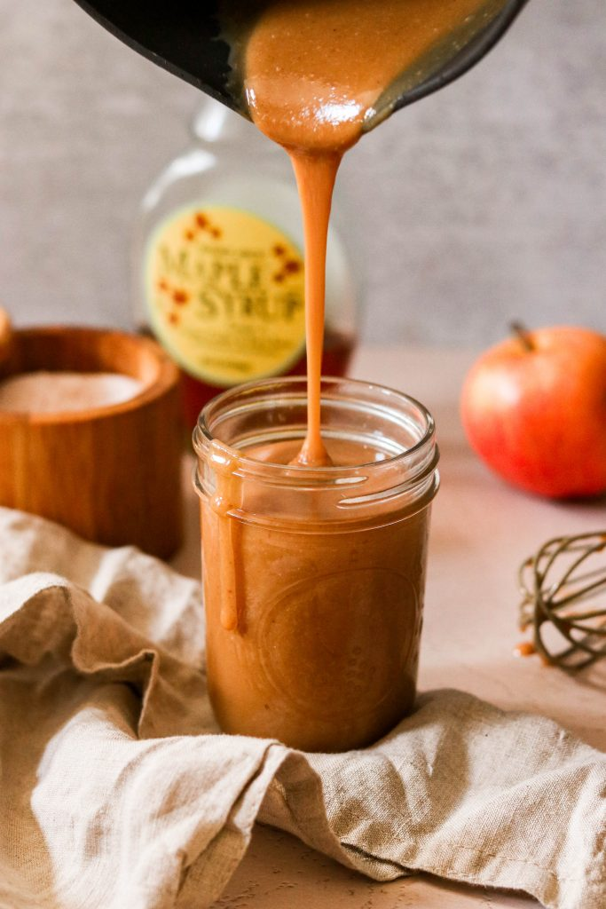 Pouring in  paleo salted caramel into a jar