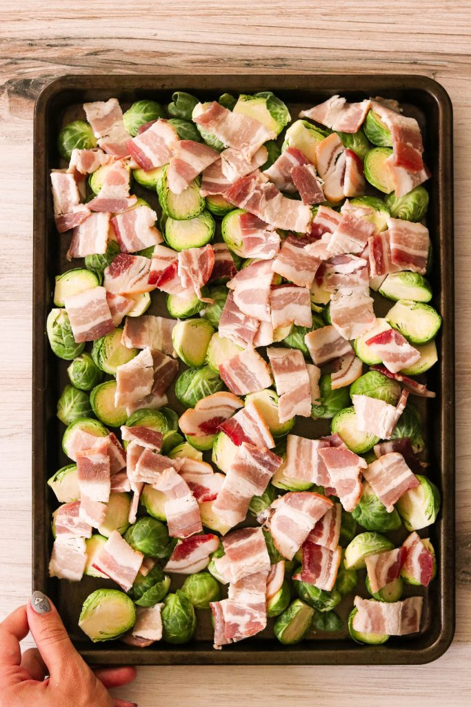 bacon and brussels sprouts on a baking sheet ready to bake