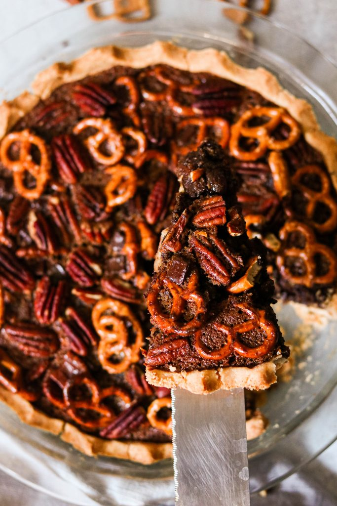 taking a slice of paleo chocolate pecan pie with pretzel topping