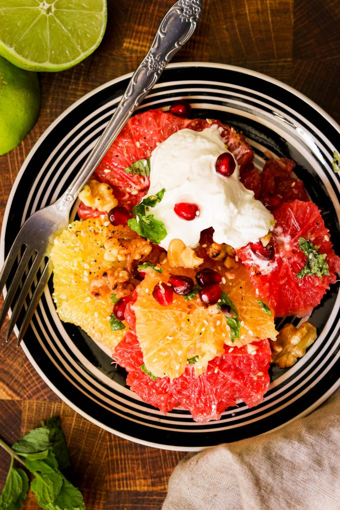 paleo winter salad with citrus on a plate ready to eat with a fork