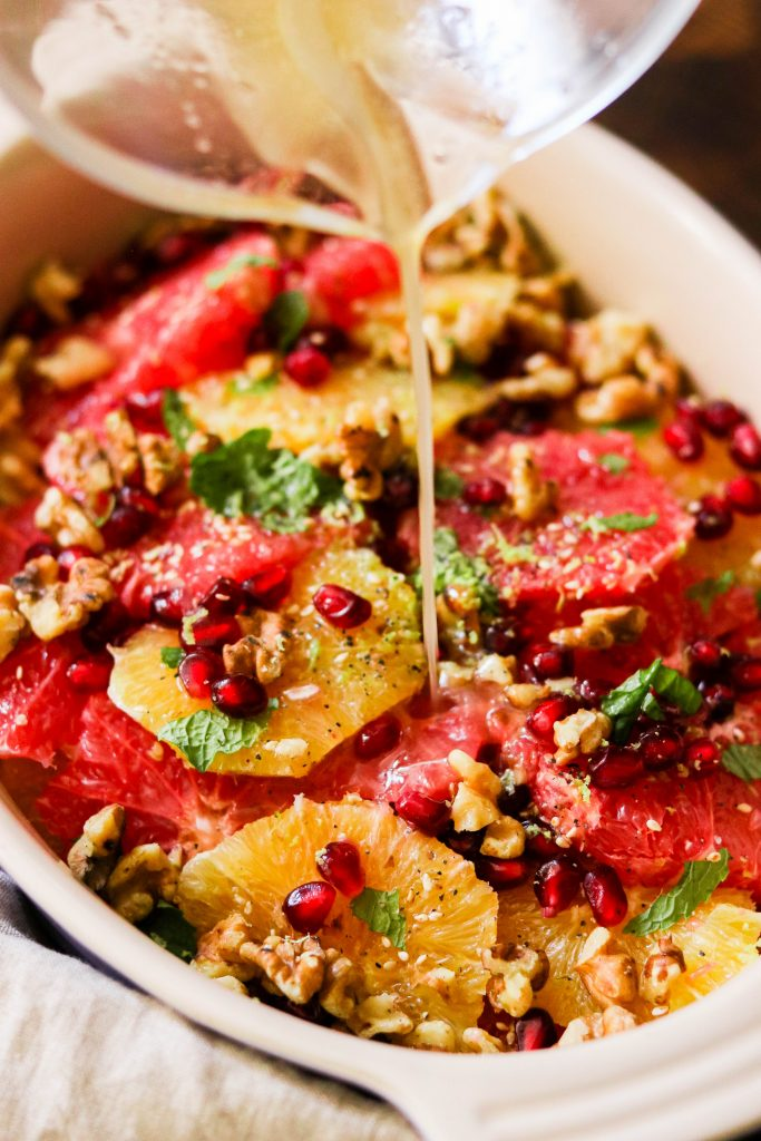 Drizzling dressing over winter citrus fruit salad
