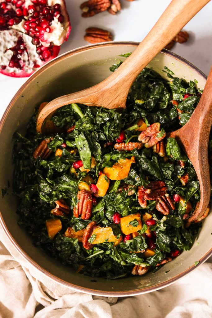 Winter kale salad with pomegranate, squash, and pecans getting tossed in a bowl