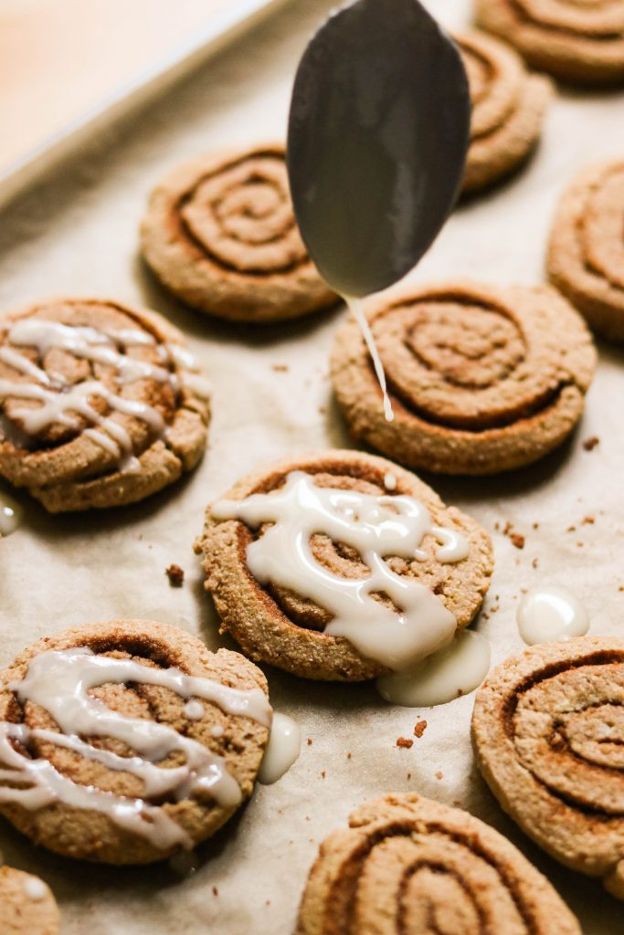 drizzling icing over cinnamon roll christmas cookies