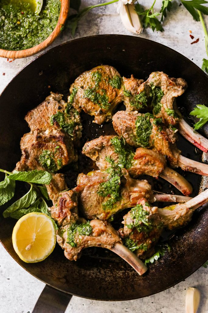 keto lamb chops in a pan, drizzled with green sauce