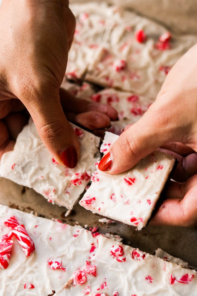 breaking up paleo dark chocolate peppermint bark with hands