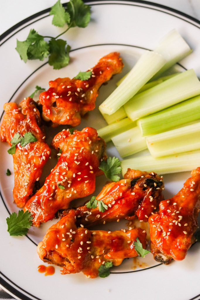 close up shot of baked honey sriracha chicken wings on a plate