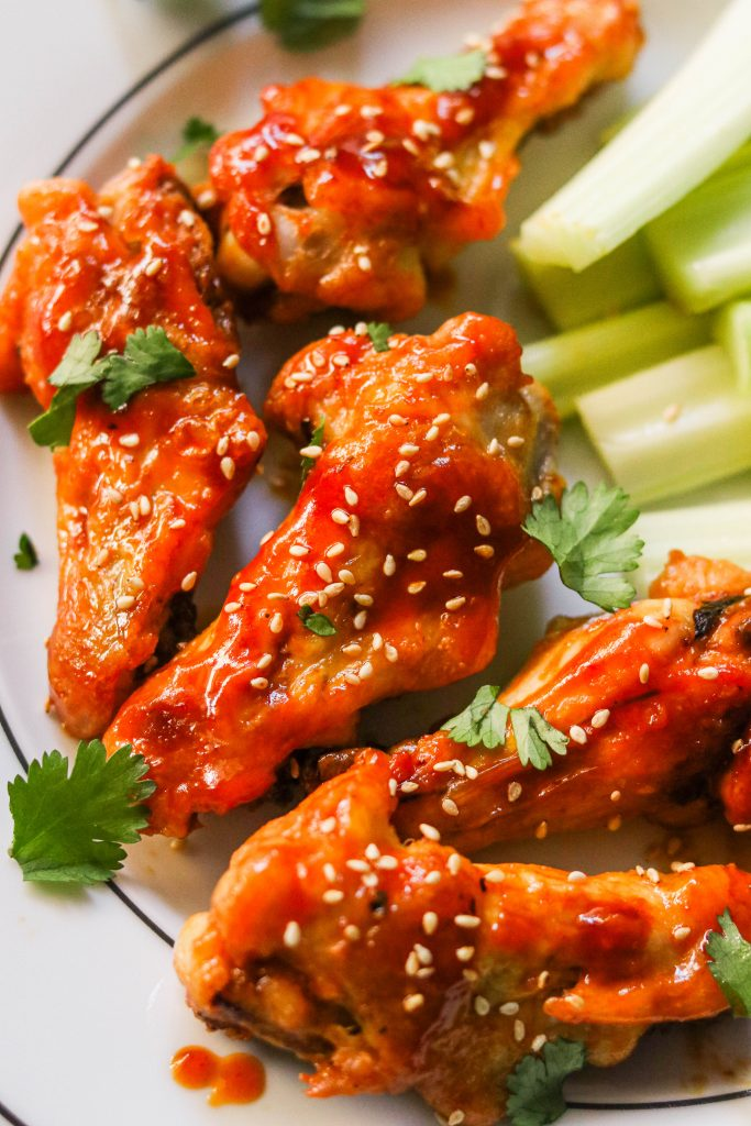 crispy honey sriracha chicken wings coated in sauce and garnished with sesame seeds and cilantro