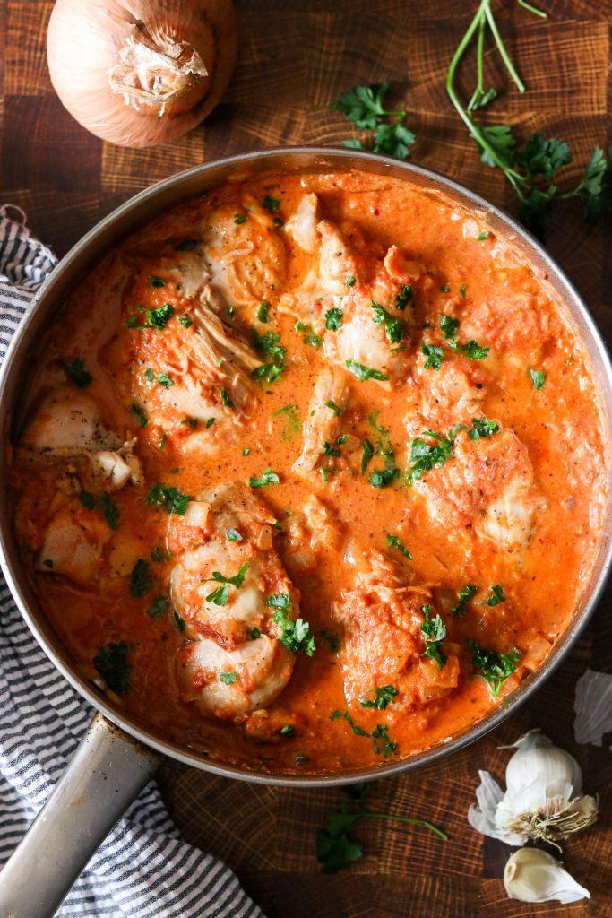 paleo skillet chicken in creamy tomato sauce garnished with parsley