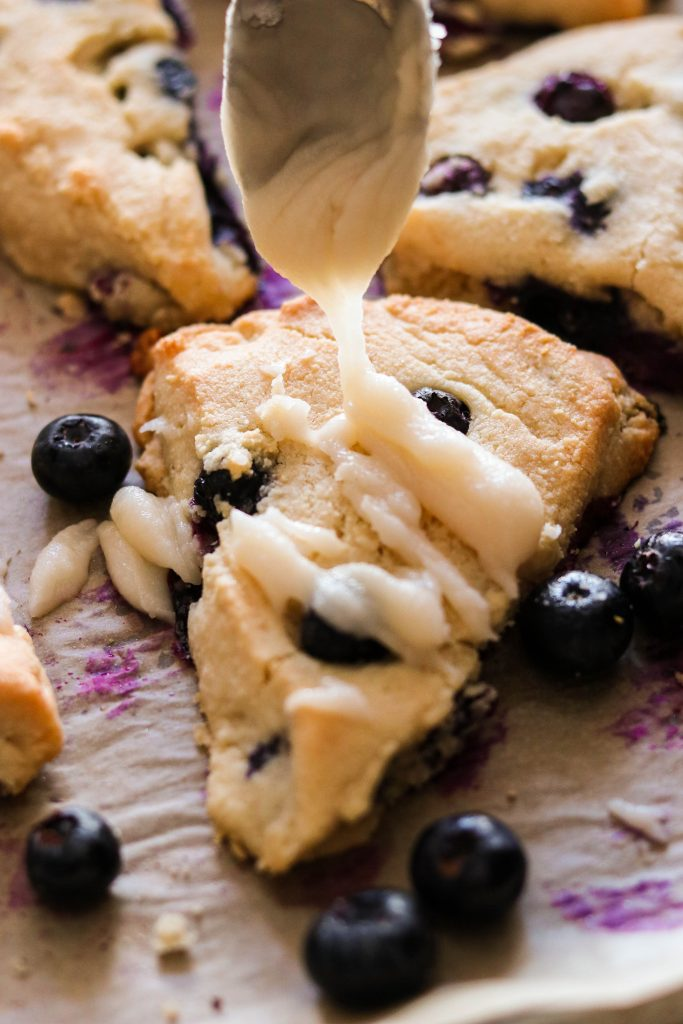 drizzling coconut glaze over almond flour blueberry scones