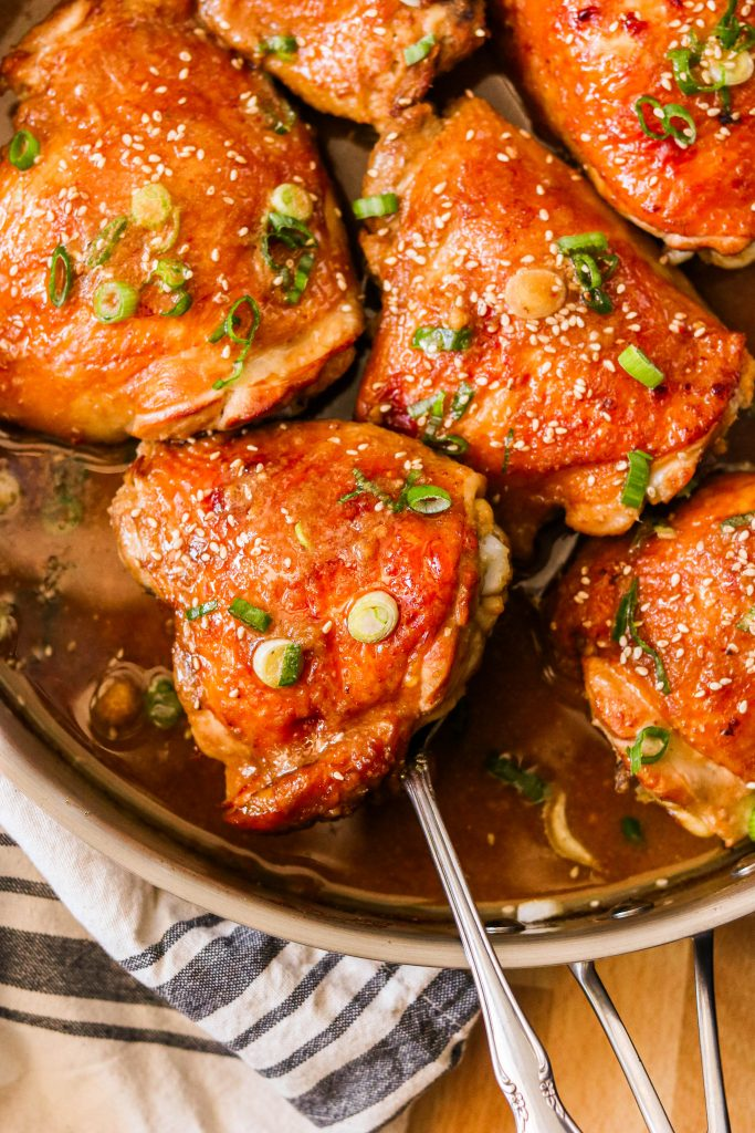baked asian chicken thighs in a pan, covered in sauce
