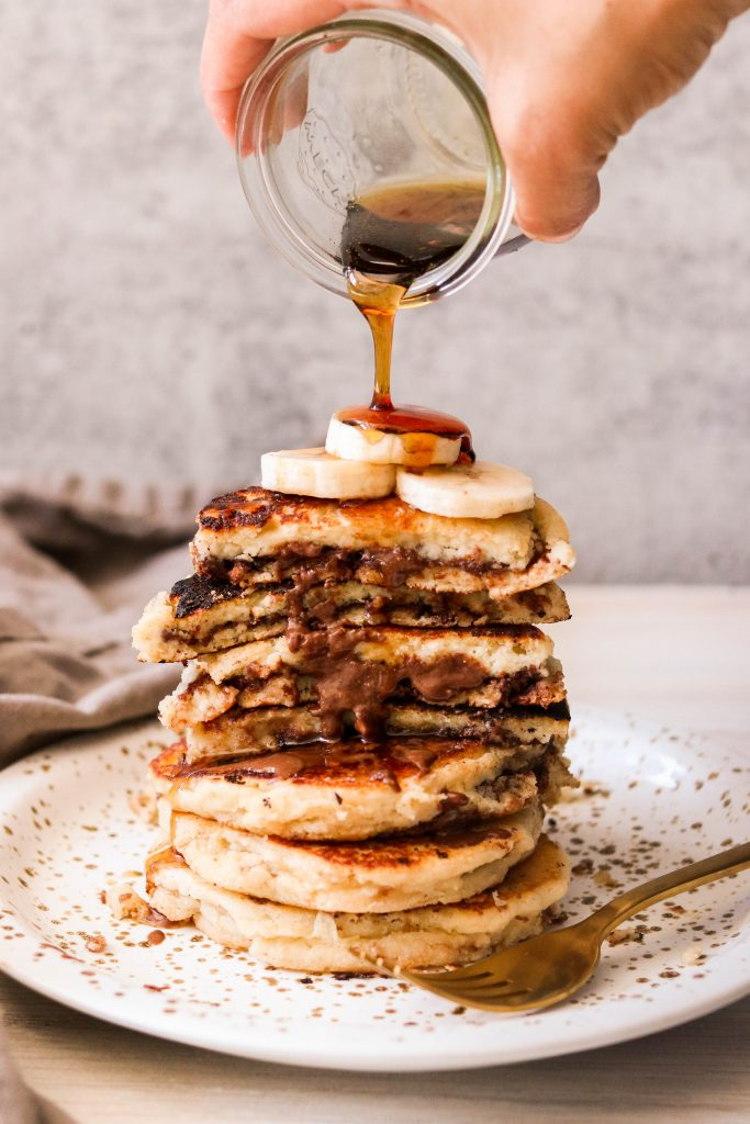 paleo chocolate stuffed pancakes getting drizzled with syrup