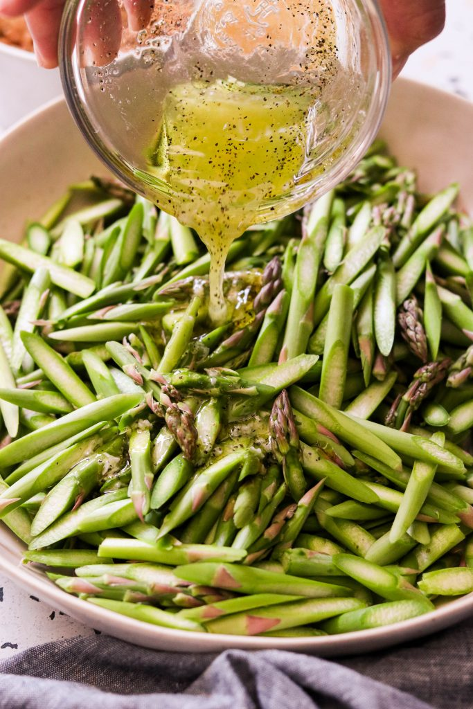 Pouring dressing over asparagus slices