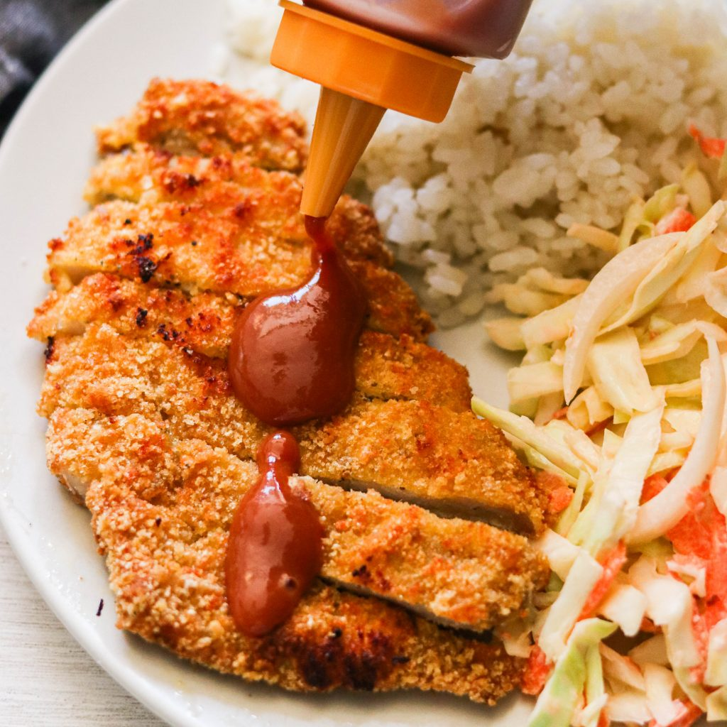 gluten free tonkatsu in the air fryer drizzled with sauce