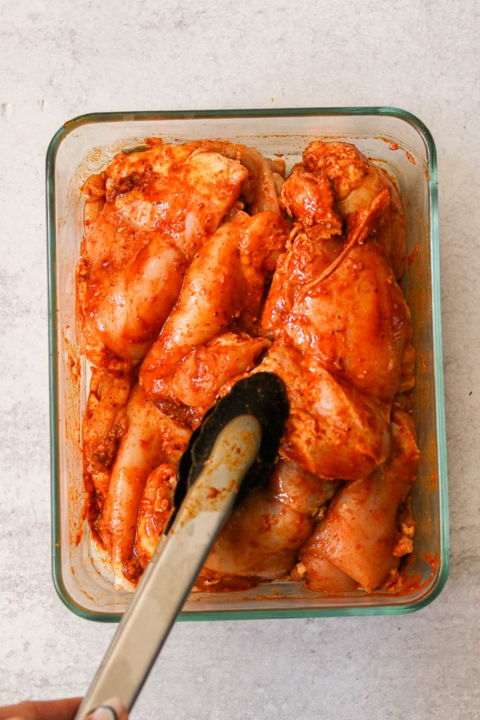 marinating paleo chicken thighs with spices in a glass container