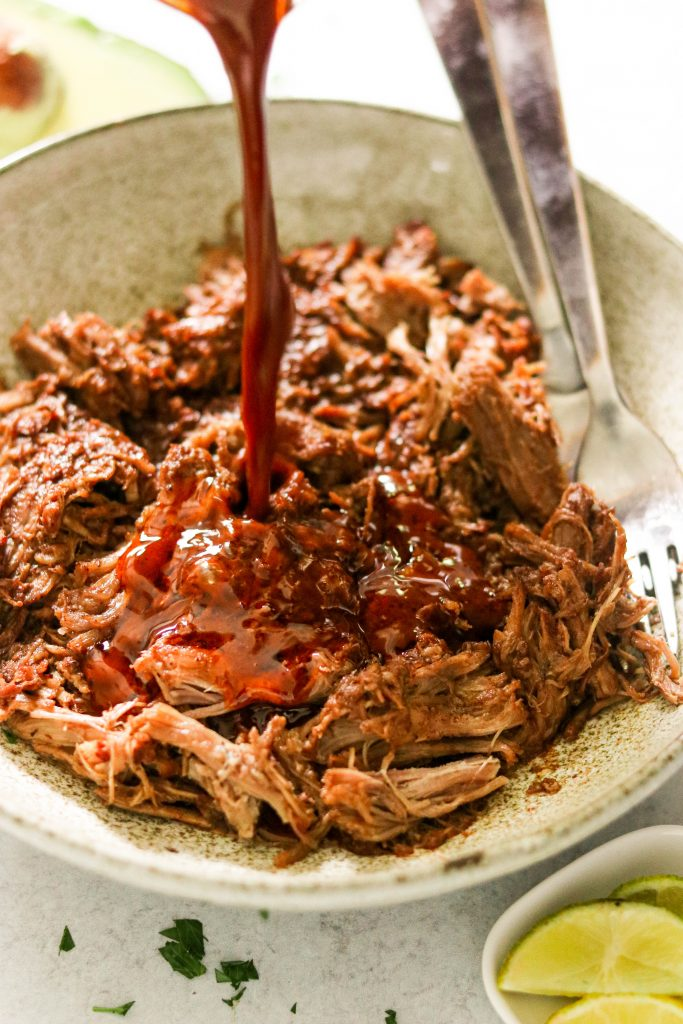 pouring mole sauce over Whole30 pulled pork