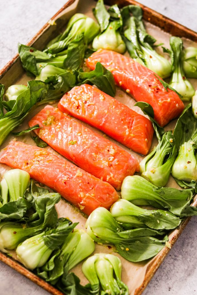 salmon and bok choy tossed with sauce and ready to bake on a sheet pan