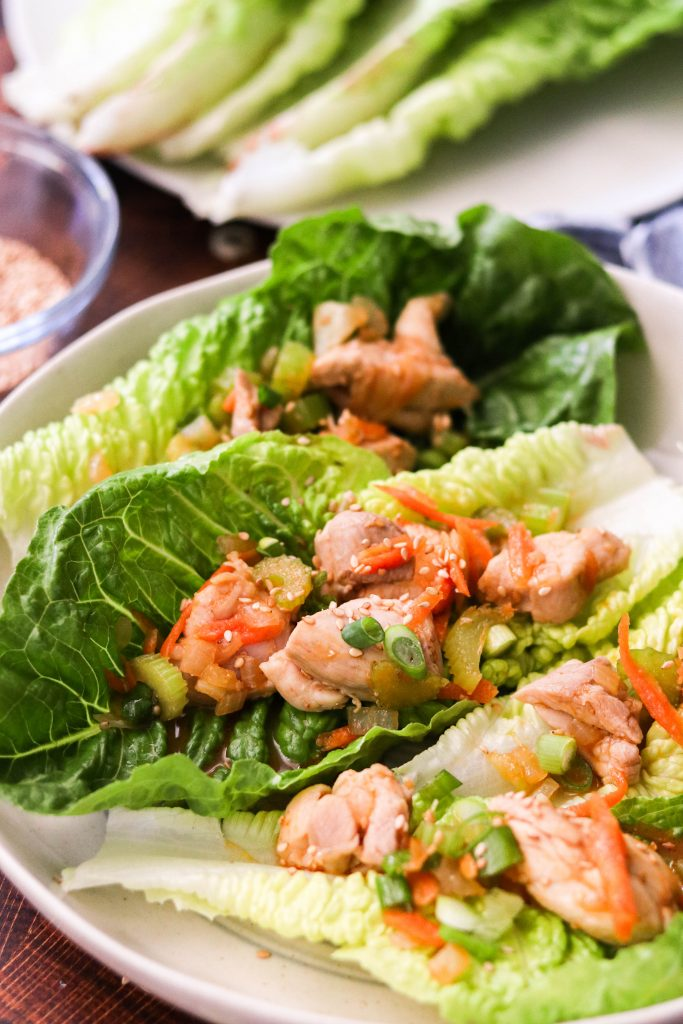 close up shot of sriracha chicken paleo lettuce wraps on a plate