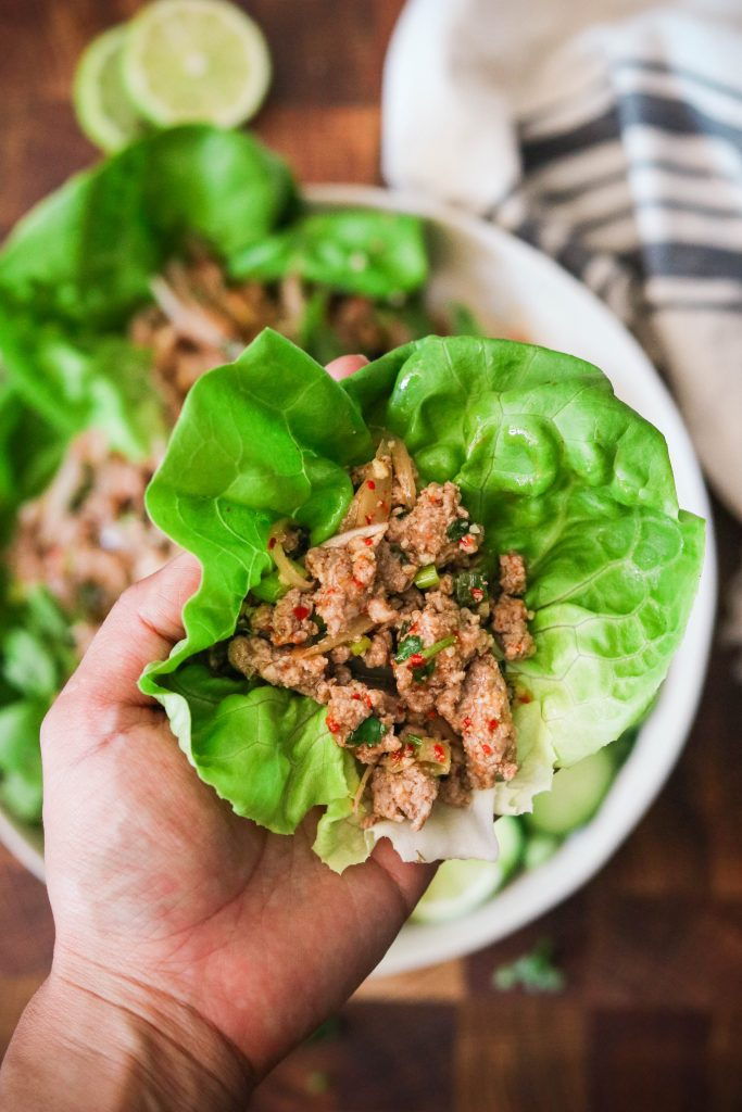 Hand lifting up keto Thai Larb in a lettuce wrap