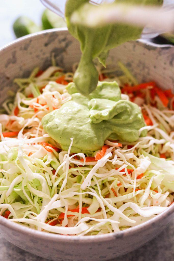 pouring avocado lime dressing over easy vegan coleslaw