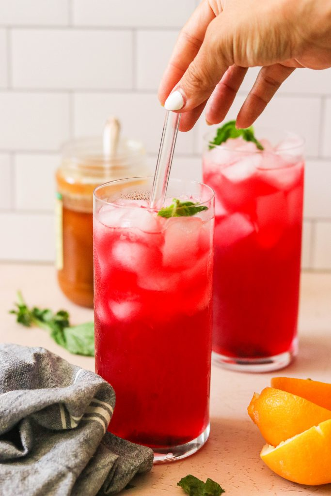 hibiscus homemade lemonade with honey poured into glass with ice with a straw in it