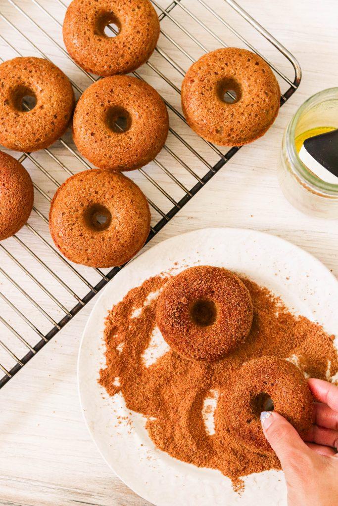 dipping paleo baked churro donuts in cinnamon sugar