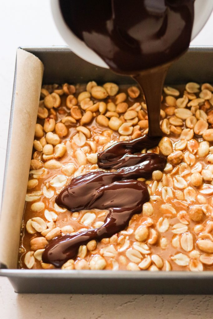 pouring chocolate over vegan snickers bars