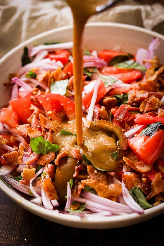 Pouring bacon fat vinaigrette over summer salad