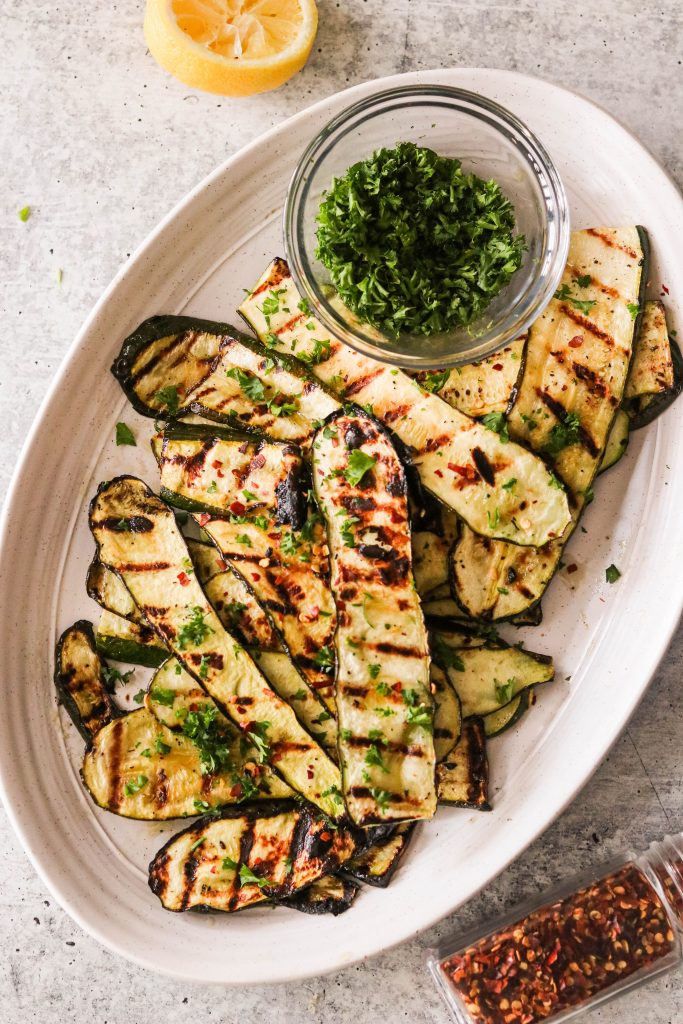 best grilled zucchini recipe on a platter with parsley