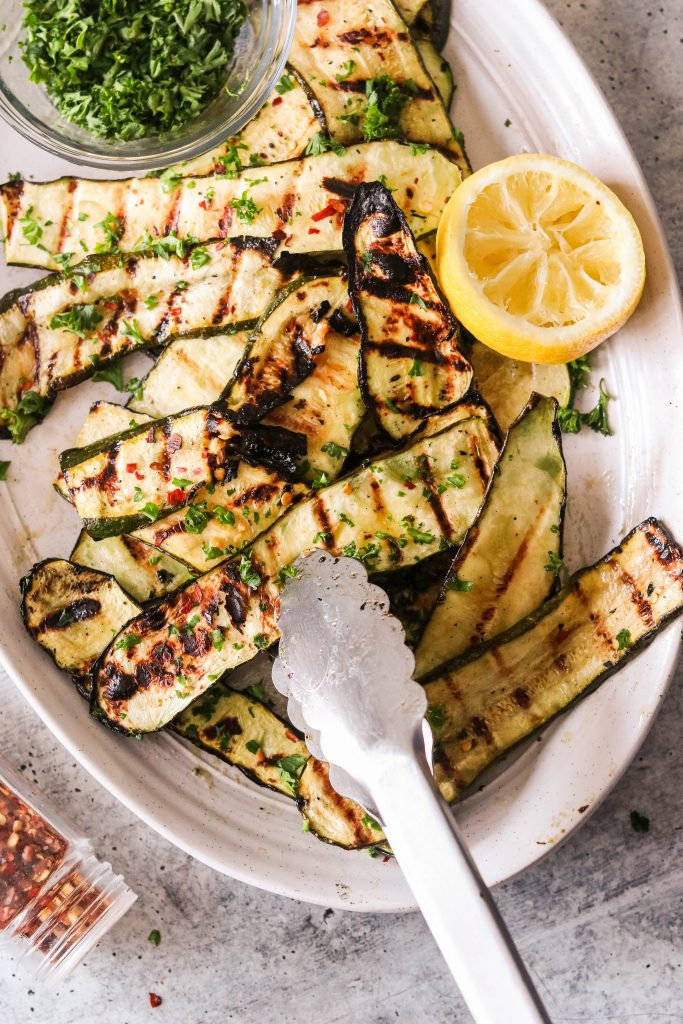 picking up grilled zucchini slices with a tong