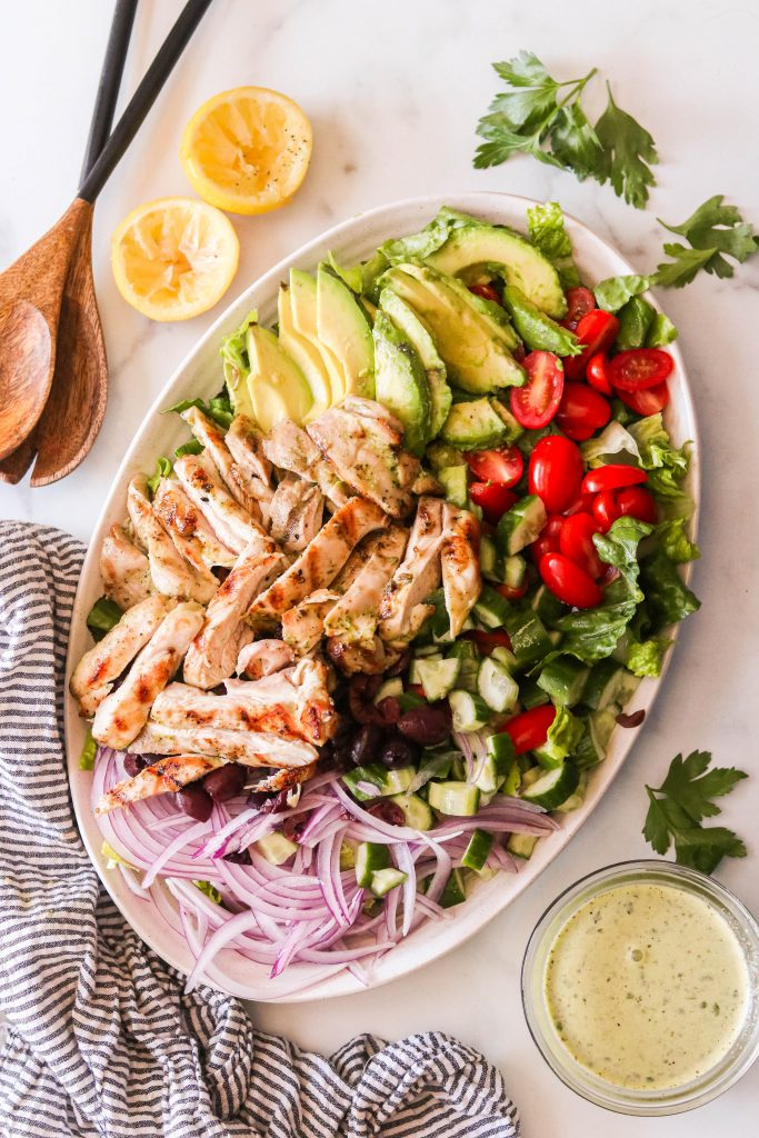 mediterranean grilled chicken salad recipe with all the ingredients on a plate before being mixed with dressing