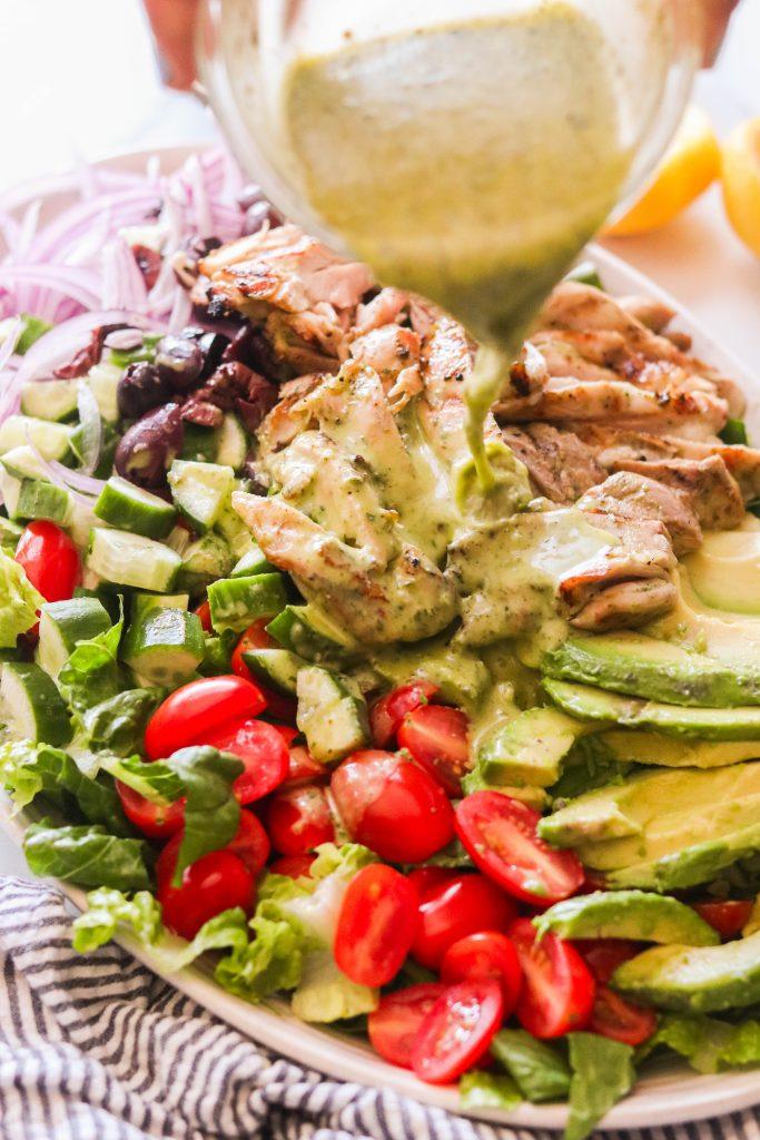 Pouring Mediterranean dressing over paleo mediterranean salad