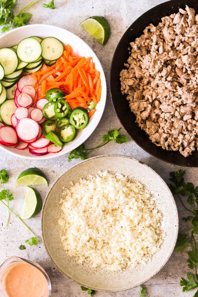 4 different components of pork banh mi bowl recipe: ground pork, pickled veggies, cauliflower rice, sriracha mayo