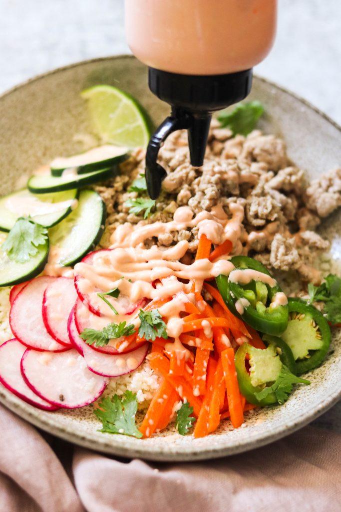 Drizzling sriracha mayo over pork, pickled veggies, and cauliflower rice
