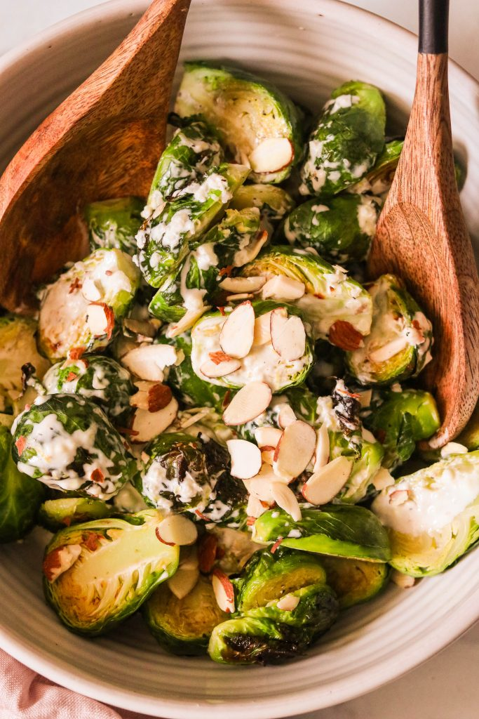 Tossing Caesar brussels sprouts together with dressing